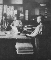 Photograph of three boys who appear to be producing/binding newspapers